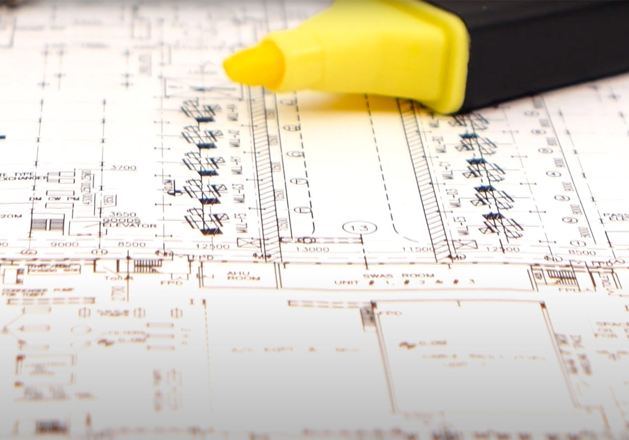 Close up image of blue print with yellow highlighter lying on top.